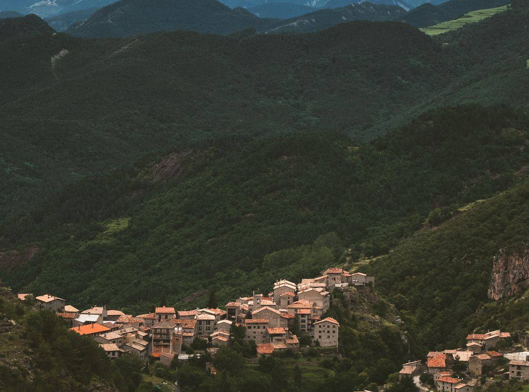 Village in the heart of the hills with snow-capped mountains in the background, visit lourdes, Hotel La Solitude