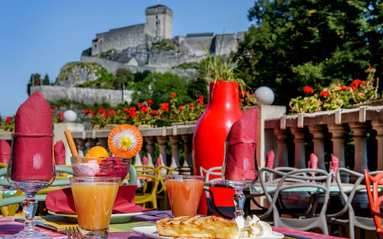Cocktails on our colorful tables on the terrace overlooking the castle, brasserie lourdes, Hotel La Solitude.