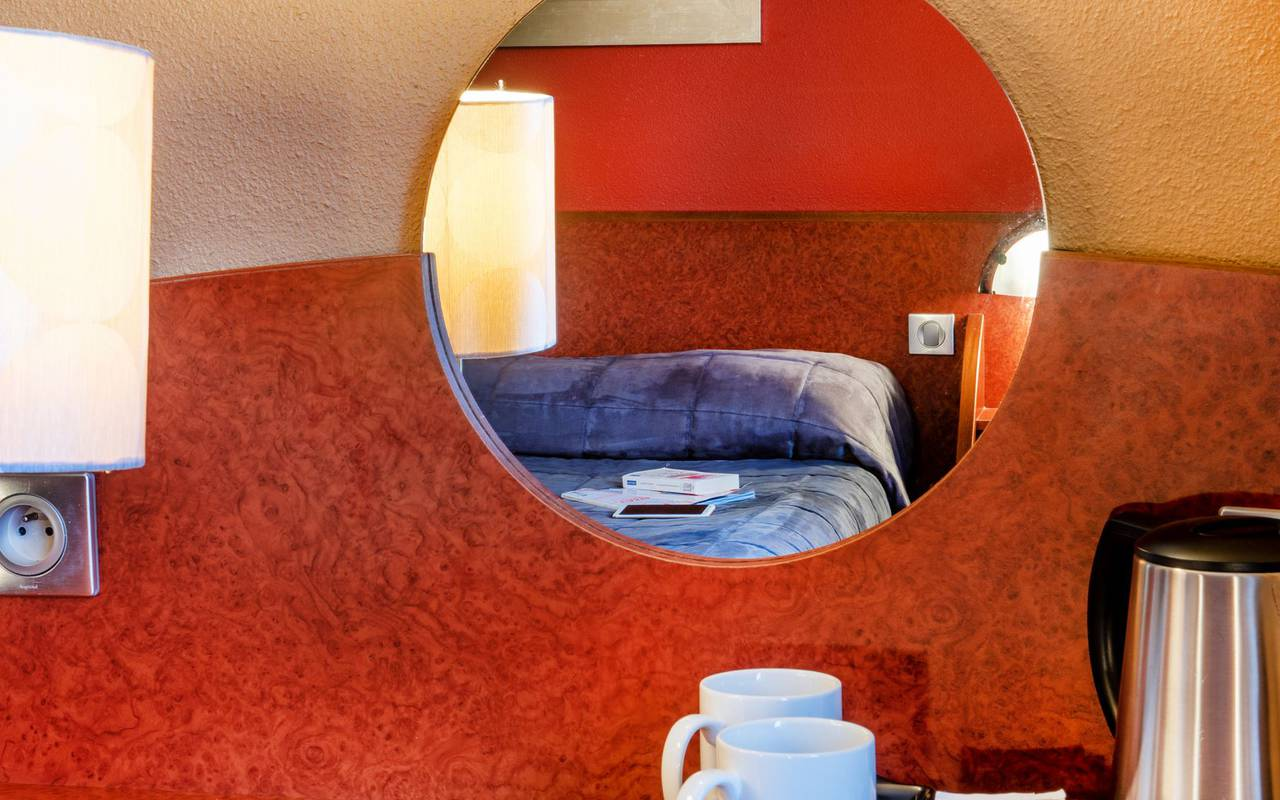 Reflection of the double bed in the mirror of the room with balcony, hotel restaurant lourdes, hotel La Solitude.