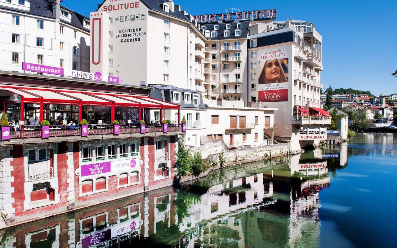Hôtel vu de l'extérieur au bord de l'eau, hotel lourdes avec piscine, Hôtel La Solitude.