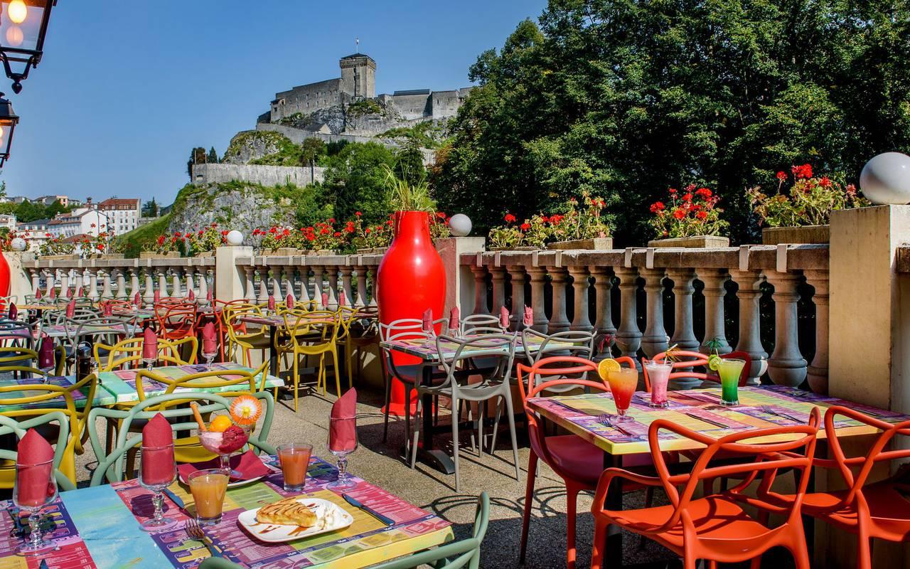 Tables colorées en terrasse au soleil, brasserie lourdes, Hôtel La Solitude.