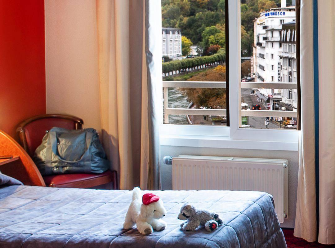 Chambre avec deux lits simples avec des peluches sur le lit et une vue sur les habitations et la nature, hotel international lourdes, Hôtel La Solitude.