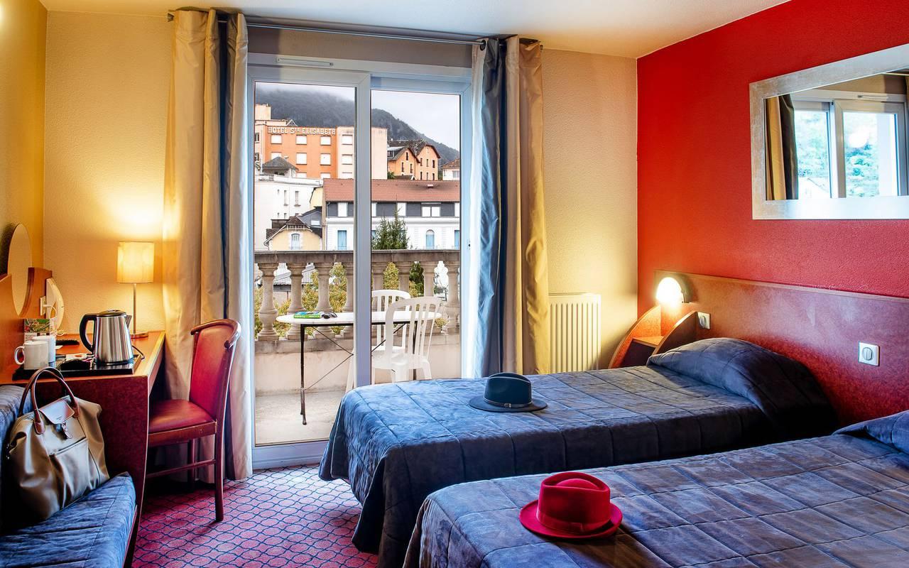 Chambre avec deux lits pour 1 personne avec table sur le balcon, hotel international lourdes, Hôtel La Solitude.