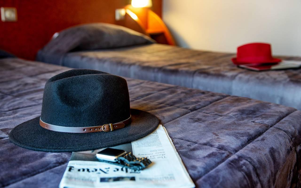 Chambre twin avec des chapeaux déposés sur chaque lit, hotel international lourdes, Hôtel La Solitude.