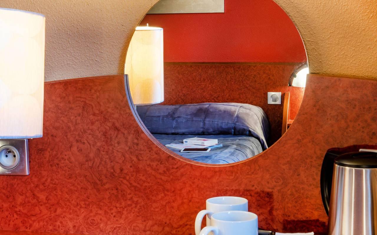 Reflet du lit double dans le miroir de la chambre avec balcon, week end detente occitanie, Hôtel La Solitude.