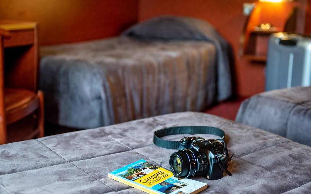 Chambre avec trois lits simples et un appareil sur l'un des lits, sejour pyrenees, Hôtel La Solitude.