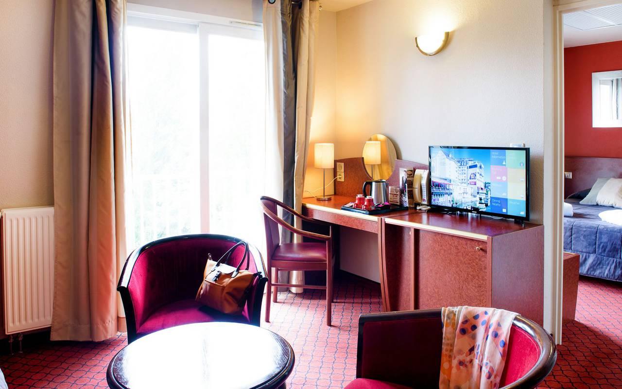 Bureau avec télévision et table de salon avec fauteuils dans la suite, sejour bien etre pyrenees, Hôtel La Solitude.